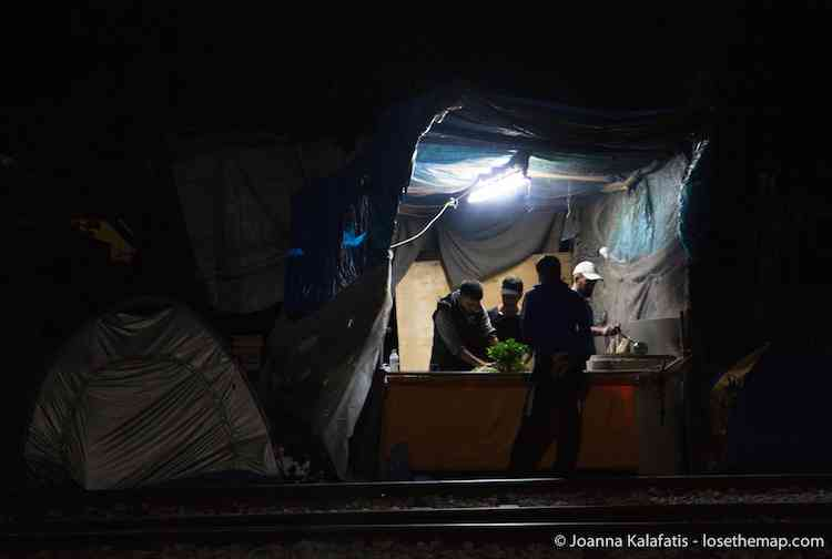A food stall run by refugees stays open late.