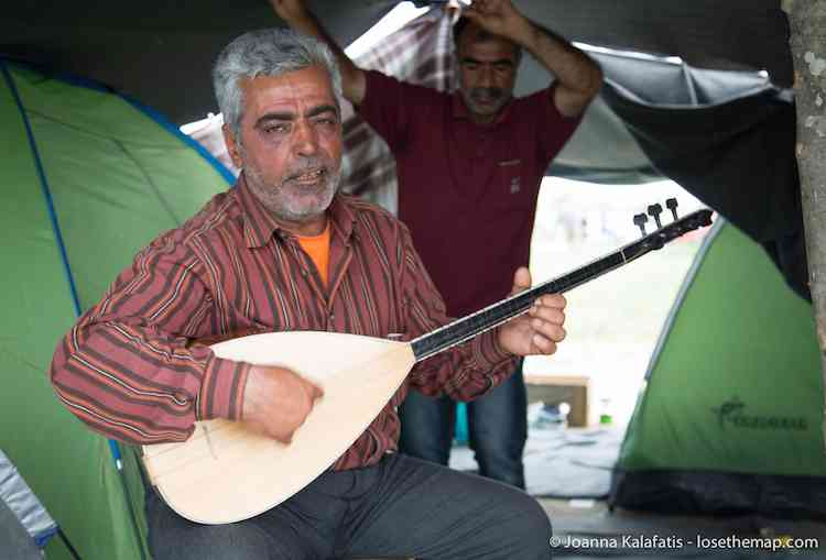 A musician continues playing day and night while his friends dance in the refugee camp.