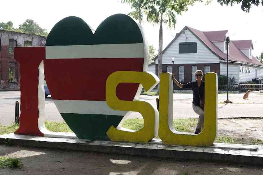 Janice in Suriname next to a sign