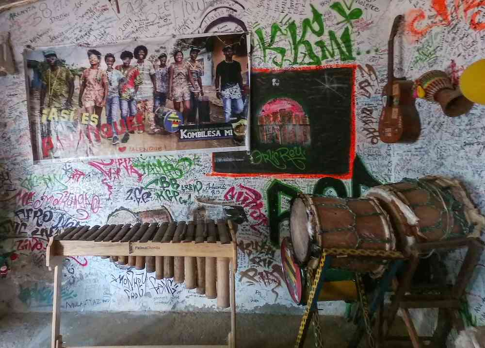 Musical instruments under a poster of Kombilesa Mi